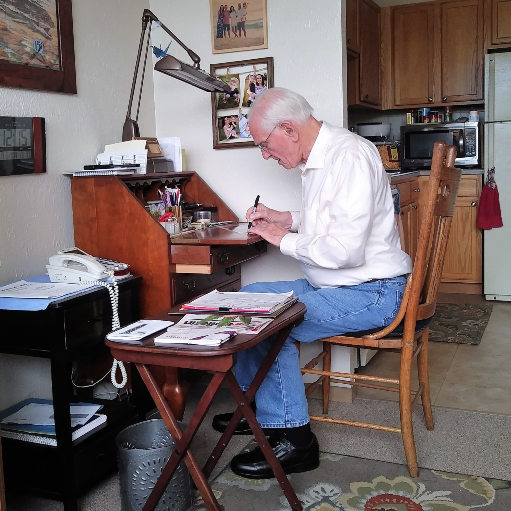 This photo shows Homer Finley at his writing desk with a pen.