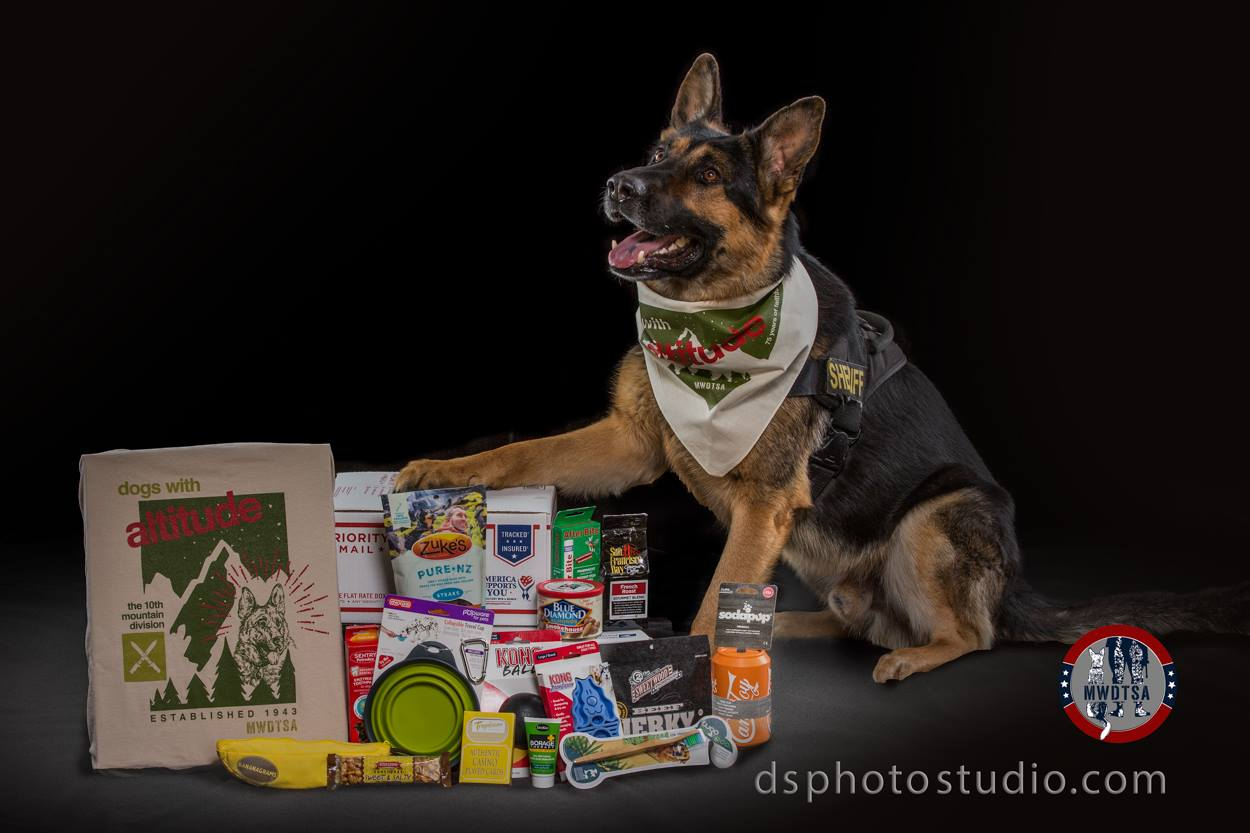 "Handsome German Shepherd police dog models ""Dogs with Altitude"" bandana and poses next to care package contents. Photo by David Schlatter Photography, Superior, Colorado."