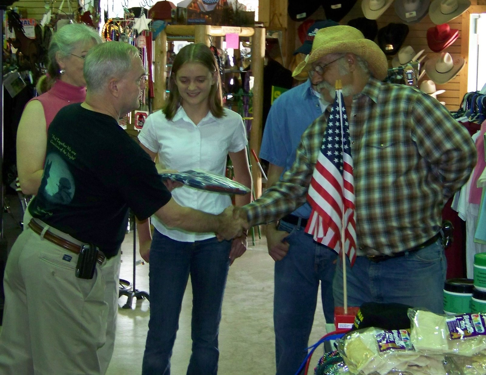 Ken Besecker presenting flag to Fabio Yepes. Sabine Yepes (store owner) and Jennifer O'Neill and Jeff Taylor (store employees) look on.