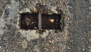 Durrance photographed the aging handle of a street sewer access lid. The image looks like a pair of square eyes, haunted with pain.