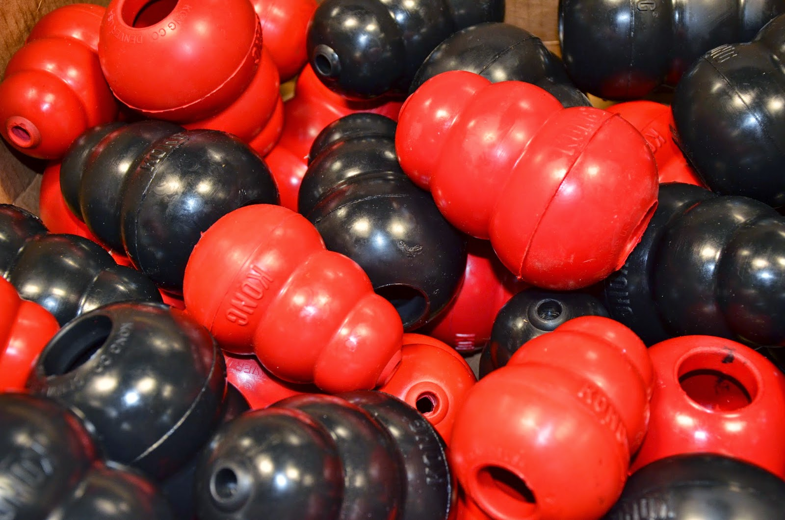 An assortment of red and black KONG toys