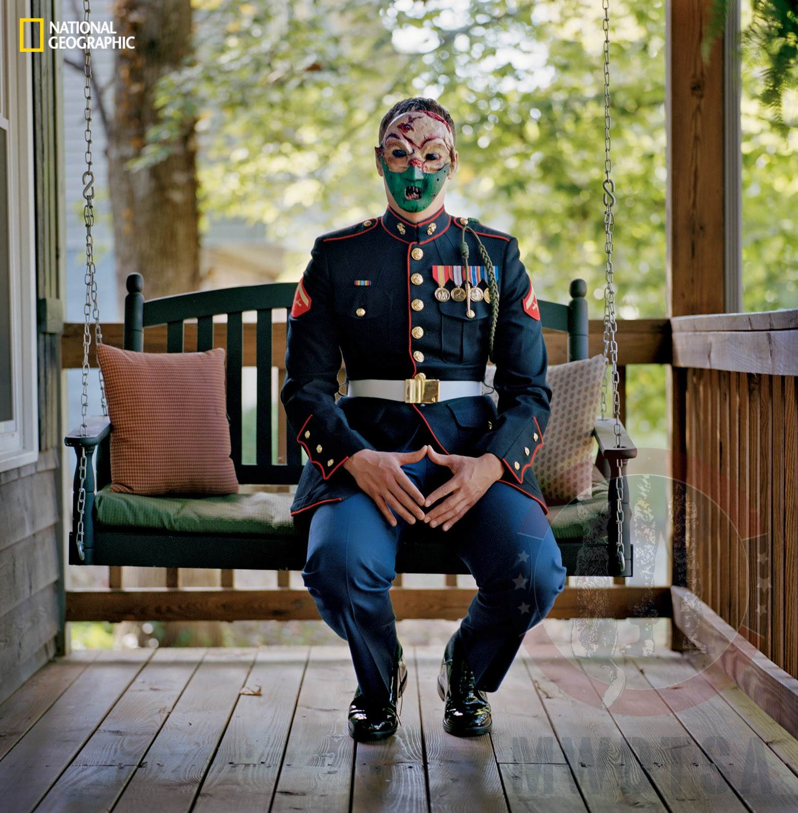 Marine Cpl. Chris McNair sitting on his parents' porch, in full uniform, wearing a mask he made in therapy.