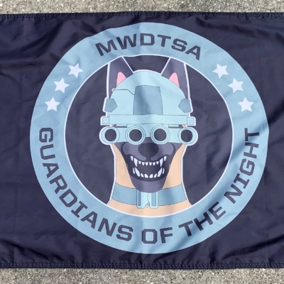 This image shows the MWDTSA Guardians of the Night flag laid out flat on a sidewalk.