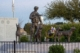 This is a 2019 photo of Military Working Dogs National Monument at Lackland Air Force Base in San Antonio, Texas. A bronze sculpture of a handler stands with his gun ready. Arrayed before him are bronze sculptures of four military working dogs representing the four main breeds used by the military. MWDTSA provided a memorial wreath, displayed on the monument. MWDTSA is providing a wreath for Memorial Day 2020, as well.