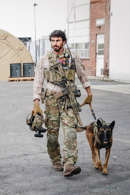 This photo shows CBS Seal Team actor Justin Melnick and his working dog Dita walking on a military base.