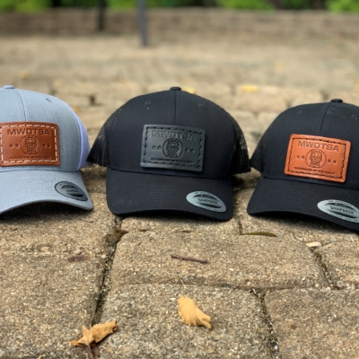This photo shows the MWDTSA FlexFit Snapback hat in three color variations: Charcoal with a brown patch, Black with a brown patch, and Black with a black patch.