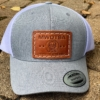 This photo shows the charcoal FlexFit Snapback hat with a brown MWDTSA patch.