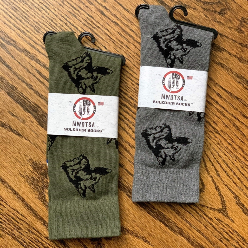 This photo shows two pairs of the handsome MMinto socks. MMinto's profile appears in a repeating pattern in black thread on the socks. This image shows the two available colors: olive and grey.