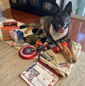 In this photo, RMWD Huba appears to be smiling while laying amidst the Honor Box goodies, which include dog treats, toys, a custom tactical vest, a blanket, a personalized certificate and more.