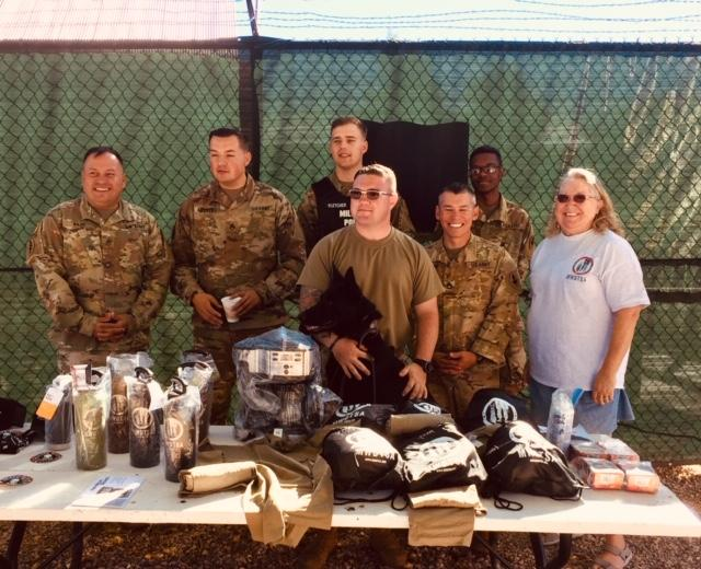This photo shows the Fort Huachuca handlers and MWDTSA volunteer Linda Costa-Bryan standing behind a picnic table loaded with MWDTSA gifts, including backpacks, FIFTY/FIFTY bottles, t-shirts, and more.