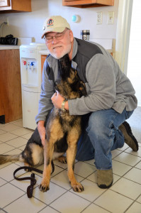 Photo shows MWDTSA volunteer Jerry Whitman receiving love from MWD Sindy.