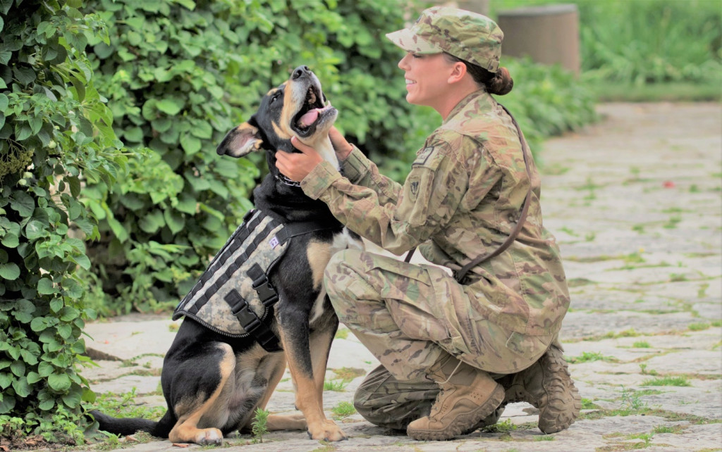 Tiffany Baker kneels with her service dog Buddy. K9s for Warriors paired Baker and Buddy, and this heart-warming photo shows the bond between them.