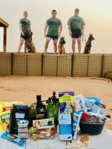 Care package contents sit on a sand bag in the foreground. Three handlers and their MWDs stand in the background modeling the 'Merica-themed MWDTSA t-shirts and MWDTSA athletic shorts that were included in the Q2-2019 care packages.