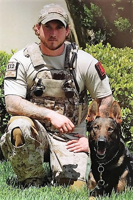 This photo shows Will Chesney in uniform, kneeling beside MWD Cairo.