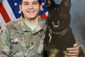 This photo shows MA2 Devon Johnson and his military working dog, MWD Kalo, posing in front of a U.S. flag. This sailor and his dog save lives.