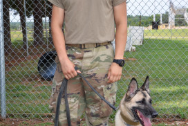 This photo shows a young Fort Campbell dog handler with his dog on leash.
