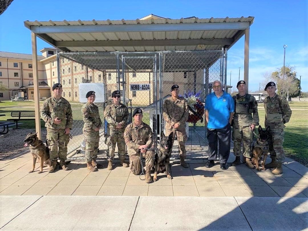 This photo shows handlers and their dogs, along with Security Forces Museum Director Ken Neal, standing in front of Nemo's Memorial at Lackland Air Force Base. In the background is a wreath donated by MWDTSA in honor of Vietnam veteran dog handler Bob Throneburg.
