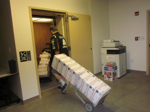 The Niwot, Colorado Postmaster and the young son of a Louisville Post Office employee wheel dollies full of care packages into an elevator on their way to the mail truck.