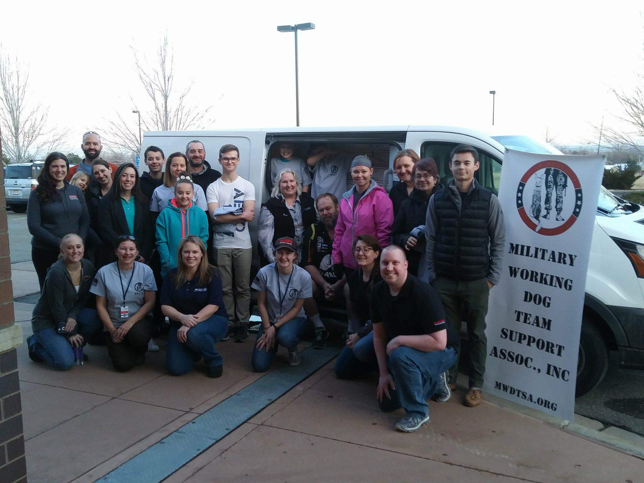 Twenty-four Q1-2018 packing volunteers pose by mail truck.
