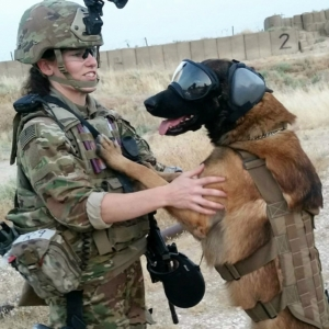 The photo on the Sponsors page shows a female service member, standing, with her MWD on his rear legs, paws on her shoulders. The MWD is wearing RexSpecs dog goggles.